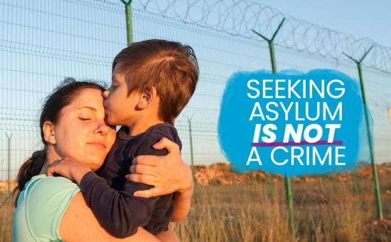 Seeking asylum is not a crime - refugee mother and child at fence